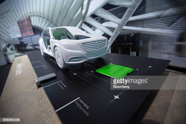 A model of a MercedesBenz S500 hydrid automobile sits parked over a wireless electrical charging station during Daimler AG's TecDay Road to the...