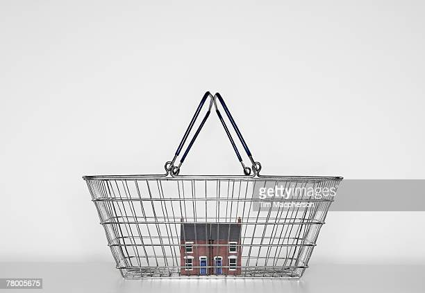 A model of a red bricked house in a shopping basket.