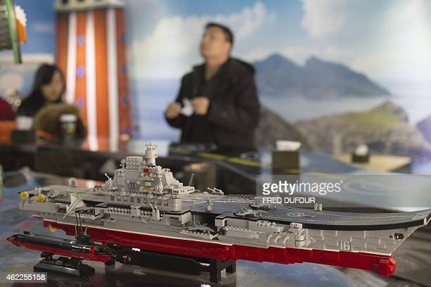 A model of China's first aircraft carrier the Liaoning is display in Beijing's Diaoyu Islands Malatang Noodle Shop on January 26 2015 Wearing a...
