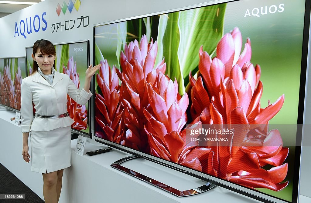 A model of Japan's electronics maker Sharp shows off new 4k liqiud crystal display (LCD) TV 'Aquos Quattron Pro' series during a press conference in Tokyo on October 22, 2013. Sharp will put 46, 52 and 60-inch models on the market on November 30 and 70 and 80-inch types on December 10. AFP PHOTO/Toru YAMANAKA