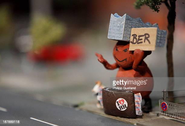 A model of the 'Elbe Philharmonic Hall Monster' holding a sign 'BER' is seen at the Miniatur Wunderland on November 13 2013 in Hamburg Germany The...
