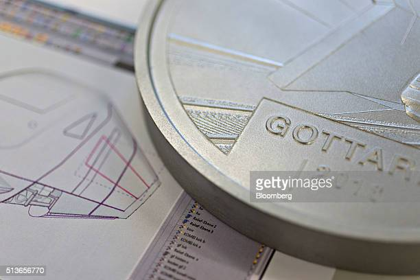A model of the Gothard Tunnel commemorative twenty Swiss franc coin sits next to a computeraided design sheet in the Swiss Confederation Swissmint in...