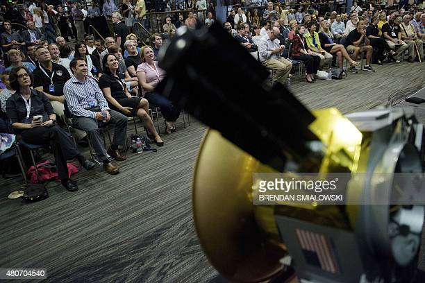 A model of the New Horizons probe is seen as people wait for telemetry from the craft at the Johns Hopkins University Applied Physics Laboratory July...