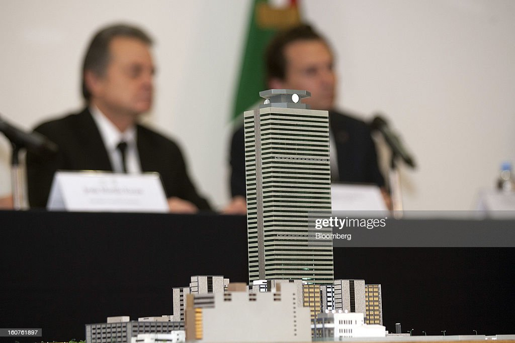 A model of the Petroleos Mexicanos (Pemex) administrative building sits in the foreground while Pedro Joaquin Coldwell, Mexico's energy minister, left, and Emilio Lozoya Austin, chief executive officer of Pemex, hold a news conference in Mexico City, Mexico, on Monday, Feb. 4, 2013. The blast that killed 37 people at state-owned oil company Petroleos Mexicanos's headquarters in Mexico City last week was caused by gas buildup, Mexico's attorney general said, the first government explanation for the nation's deadliest explosion since 2006. Photographer: Susana Gonzalez/Bloomberg via Getty Images