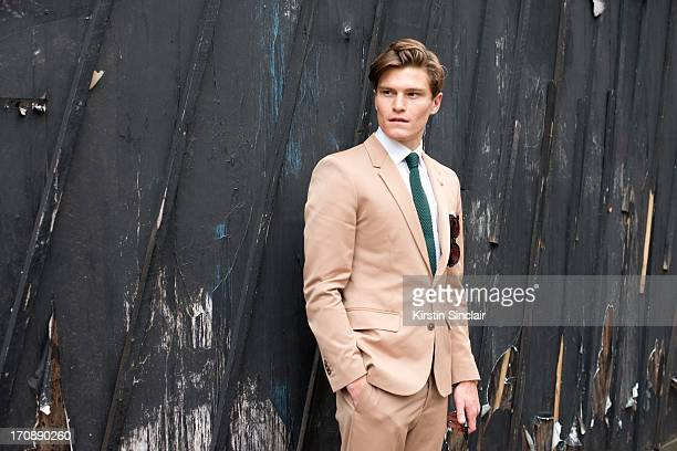 Model Oliver Cheshire wears a Martin Margiela suit Reiss Shirt and Respect sunglasses on day 2 of London Collections Men on June 17 2013 in London...