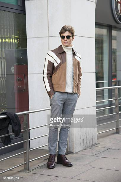 Model Oliver Cheshire wears a Neil Barrett jacket Reiss sweater and trousers Ray Ban sunglasses and Marks and Spencers shoes day 1 of London Mens...