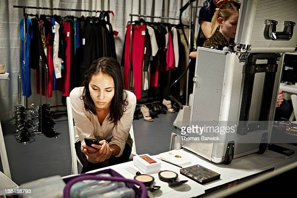 Model on smart phone backstage at a fashion show