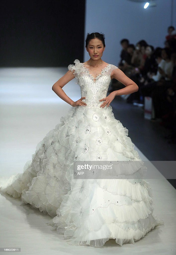 A model parades a creation from the Galatea Wedding Dress Collection during the China Fashion Week in Beijing on October 27, 2013. China Fashion Week runs from October 25 to November 1. CHINA OUT AFP PHOTO