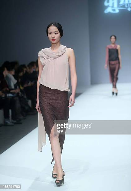 A model parades a creation from the LIANVIS Lian Huiqing Collection during the China Fashion Week in Beijing on October 30 2013 China Fashion Week...