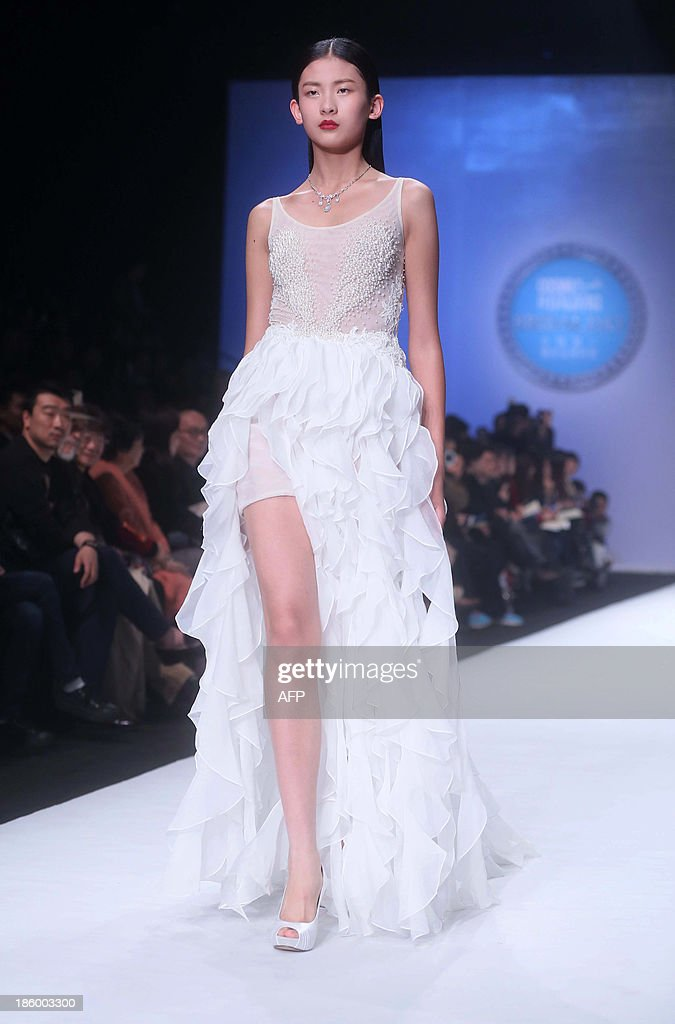 A model parades creations of the Allwhite Peng Jing Wedding Dress Collection during China Fashion Week in Beijing on October 27, 2013. China Fashion Week runs from October 25 to November 1. CHINA