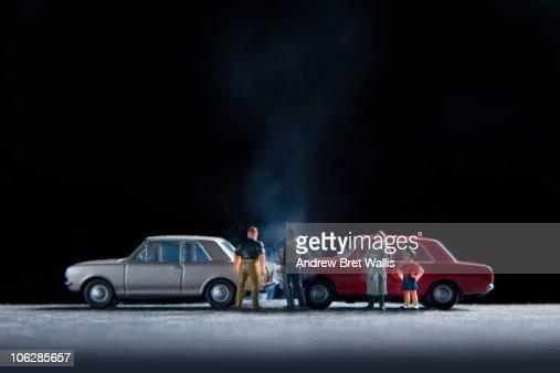 model people gathered around a model car crash