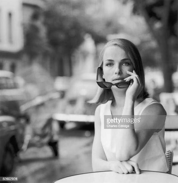 A model pictured removing her sunglasses in the Rue De Seine Paris early 1960s