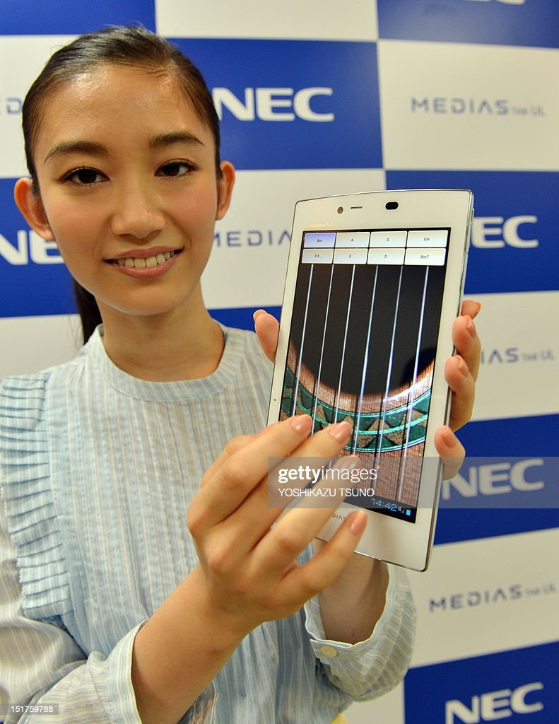 A model plays a virtual guitar on a new tablet device from Japanese electronics manufacturer NEC called 'Medias Tab N-08D' at a preview in Tokyo on September 11, 2012. The new tablet, equipped with a seven-inch touch-screen display, weighs only 249g and will go on sale on September 20 through Japan's mobile communication company NTT DoCoMo. AFP PHOTO / Yoshikazu TSUNO