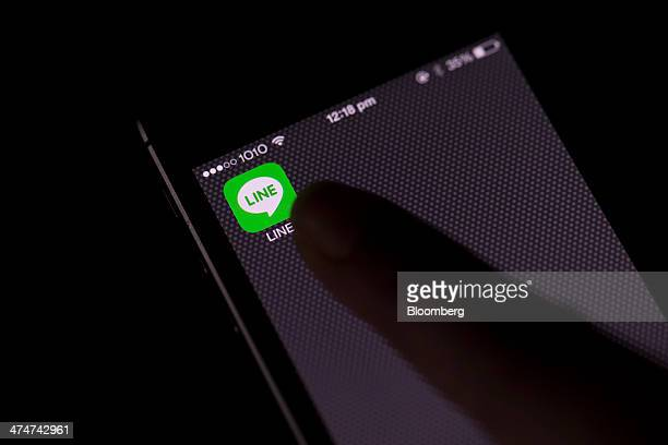 A model points to an application icon for Line Corp's internet messaging and calling service controlled by Naver Corp displayed on an Apple Inc Phone...