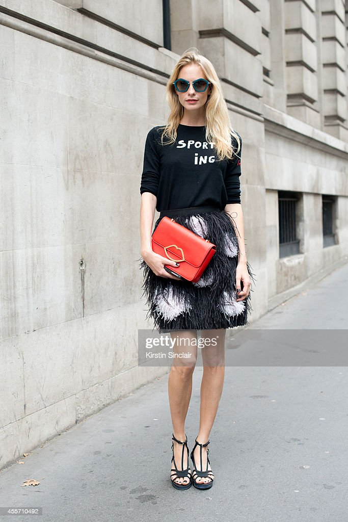 Model Poppy Delevingne is wearing Chanel shoes, Miu Miu sunglasses, Mathew Williamson skirt, Bella Freud top and Lulu Guinness bag on day 3 of London Collections: Women on September 14, 2014 in London, England.