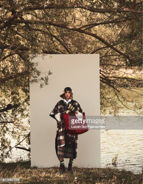 Model poses at a fashion shoot for Madame Figaro on September 12 2017 in Paris France Coat cardigan shirt skirt tote gloves socks and boots cap...