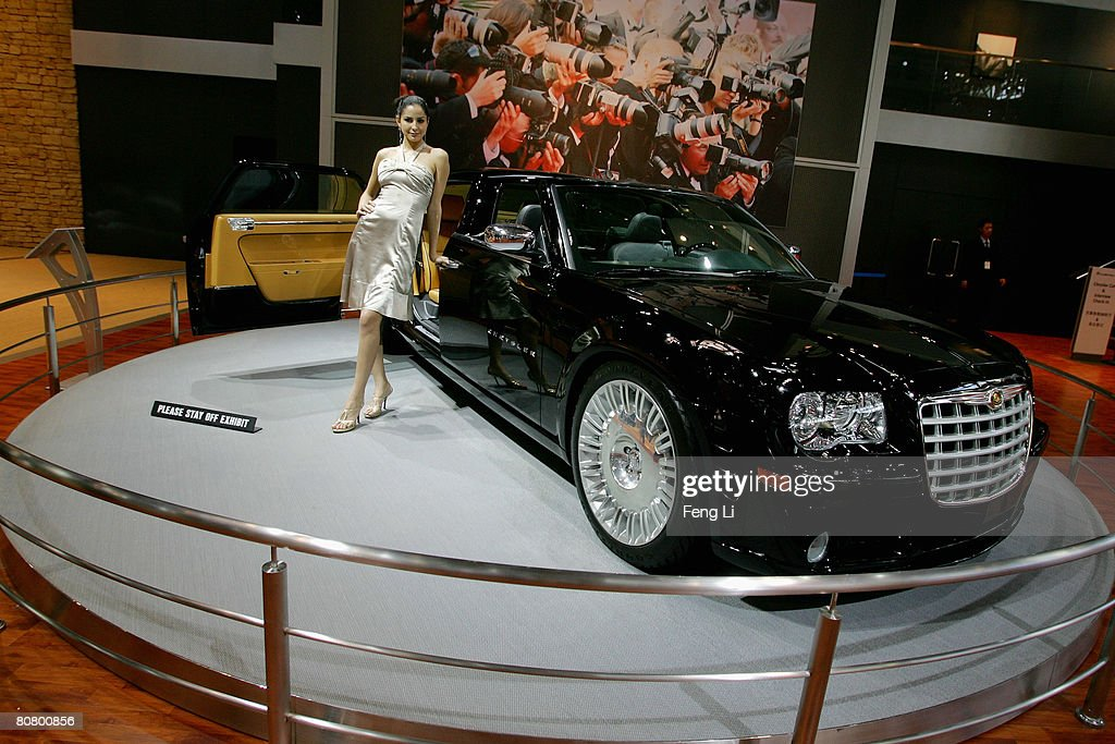 A model poses beside the Chrysler Hollywood during a special media opening of the Auto China 2008 show at the new China International Exhibition Center on April 21, 2008 in Beijing, China. The annual auto show is held from April 20-28 with 890 vehicles including 55 concept cars on show.