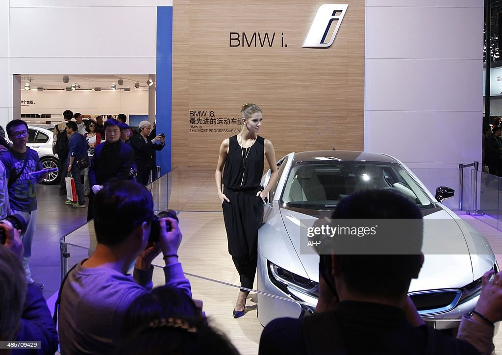 A model (C) poses by a BMW i8 car on display at the China International Exhibition Center new venue during the 'Auto China 2014' Beijing International Automotive Exhibition in Beijing on April 20, 2014. Leading automakers are gathering in Beijing for the kickoff of China's biggest car show, but lackluster growth and environmental restrictions in the world's largest car market have thrown uncertainty into the mix. More than 1,100 vehicles are being showcased at the auto show, which opens to the public on April 21. CHINA