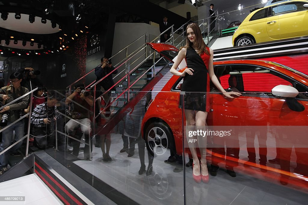 A model (C) poses by a Fiat car on display at the China International Exhibition Center new venue during the 'Auto China 2014' Beijing International Automotive Exhibition in Beijing on April 20, 2014. Leading automakers are gathering in Beijing for the kickoff of China's biggest car show, but lackluster growth and environmental restrictions in the world's largest car market have thrown uncertainty into the mix. More than 1,100 vehicles are being showcased at the auto show, which opens to the public on April 21. CHINA