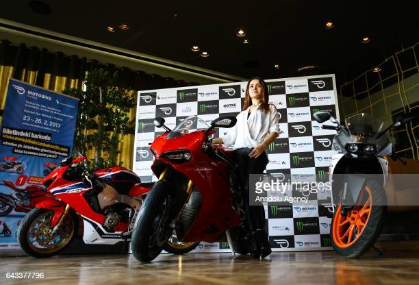 A model poses for a photo near a motorbike during an introductory meeting of Motobike exhibition organized by Messe Frankfurt Istanbul in Istanbul...