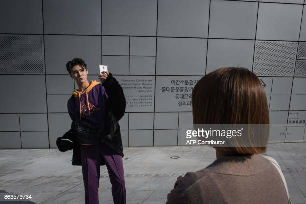 A model poses for a selfie during Seoul fashion week at Dongdaemun Design Plaza in Seoul on October 20 2017 For Seoul's flamboyant followers of...