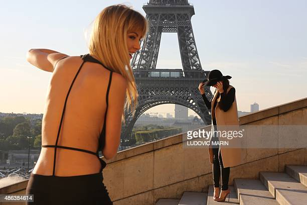 A model poses for a shooting in front of the Eiffel tower at sunrise on september 3 in Paris AFP PHOTO / LUDOVIC MARIN