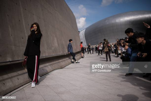 A model poses for photographers during Seoul Fashion Week at Dongdaemun Design Plaza in Seoul on October 19 2017 For Seoul's flamboyant followers of...
