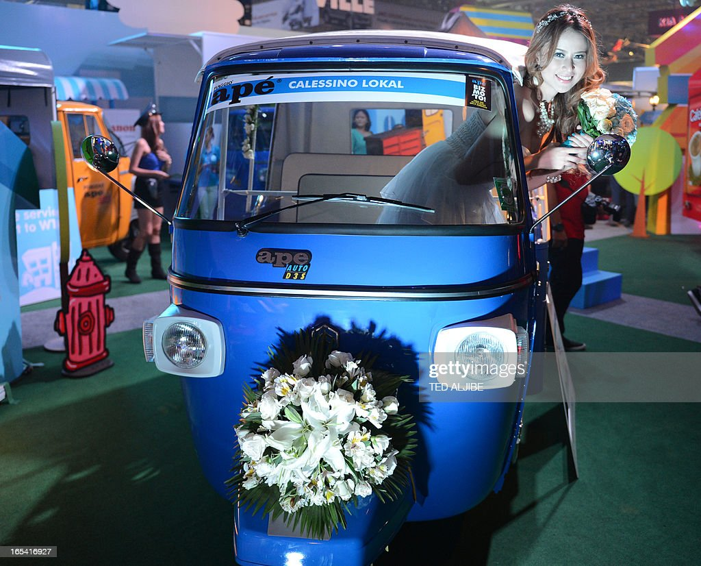 A model poses for photos inside a three-wheeled vehicle displayed at the auto show in Manila on April 4, 2013. The annual auto show is being held from April 4 to 7 at the world trade center.