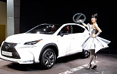 A model poses next a Lexus NX 200i during the second press day of the Paris Motor Show on October 03 in Paris France The Paris Motor Show will...