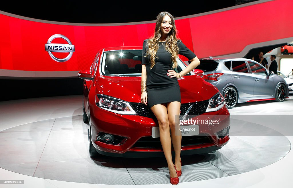 A model poses next a Pulsar produced by Nissan during the press day of the Paris Motor Show on October 02, 2014, in Paris, France. The Paris Motor Show will showcase the latest models from the auto industry's leading manufacturers at the Paris Expo exhibition centre.