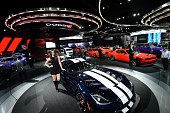 A model poses next to a 2016 Dodge Fiber ACE during the press preview of the 2016 North American International Auto Show in Detroit Michigan on...
