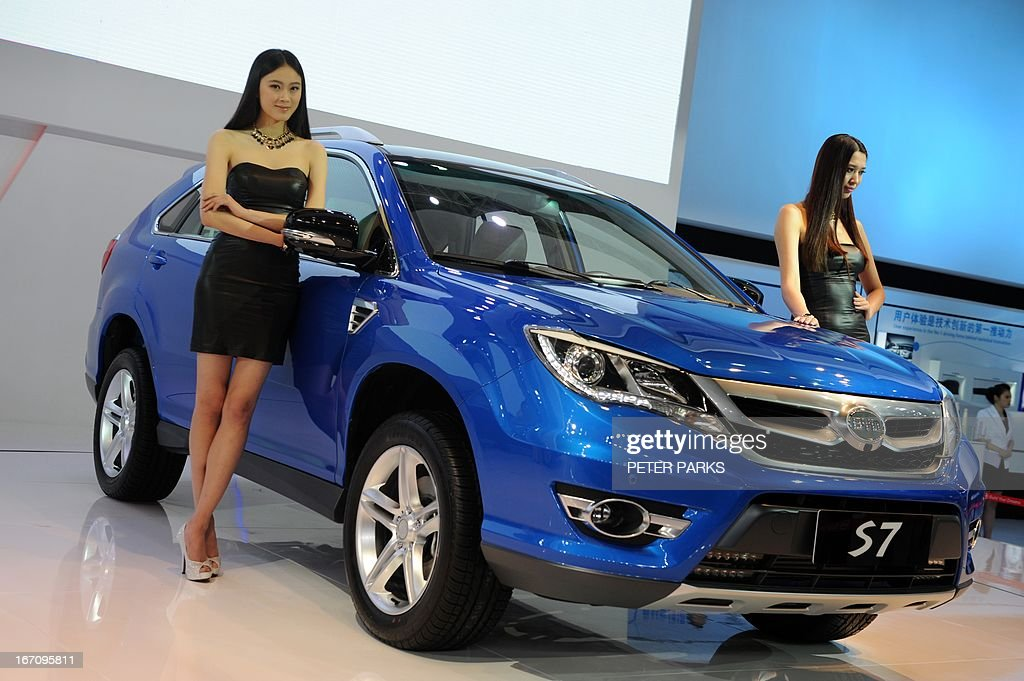 A model poses next to a BYD S7 SUV on media day at the Shanghai auto show in Shanghai on April 20, 2013. Chinese carmaker BYD gave pride of place to its new S7 at the show while another of its models, a fully-electric vehicle, languished in a corner with only a handful of visitors, a contrast which is indicative of the battle in the auto sector with gas-guzzling SUVs blazing past green-energy cars despite state incentives to promote cleaner vehicles in a bid to tackle the country's air pollution crisis. AFP PHOTO/Peter PARKS