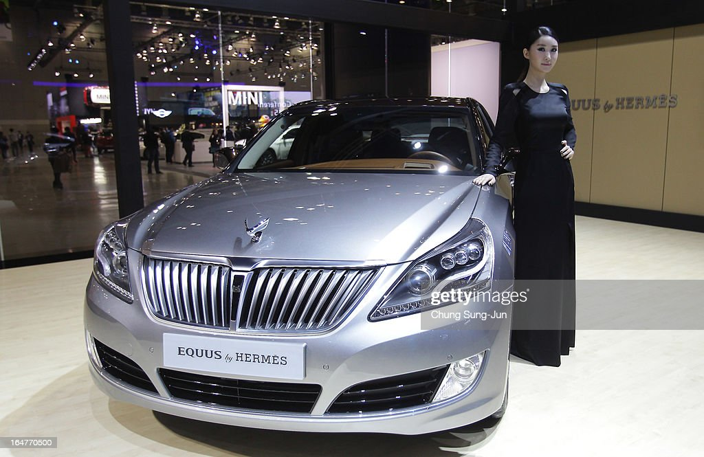 A Model poses next to a Hyundai Equus Hermes at the Seoul Motor Show 2013 on March 28, 2013 in Goyang, South Korea. The Seoul Motor Show 2013 will be held in March 29-April 7, featuring state-of-the-art technologies and concept cars from global automakers. The show is its ninth since the first one was held in 1995. About 384 companies from 14 countries, including auto parts manufacturers and tire makers, will set up booths to showcase trends in their respective industries, and to promote their latest products during the show.