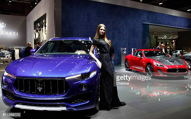 A model poses next to a Maserati Levante automobile during the second press day of the Paris Motor Show on September 30 in Paris France The Paris...