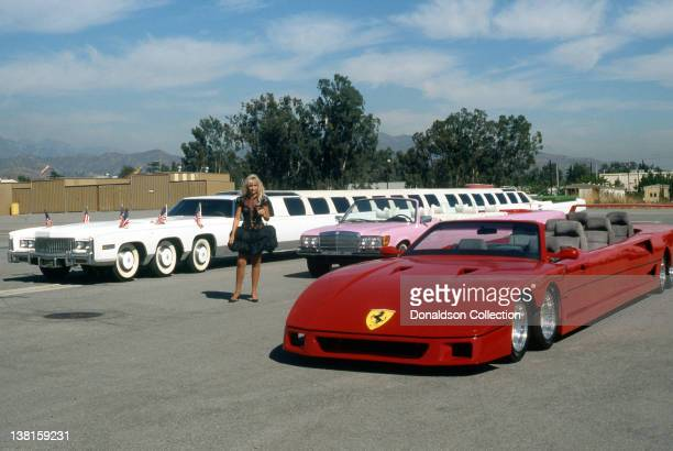 A model poses next to giant whimsical custom built Cadillac Mercedes and Ferrari stretch limousines designed by Jay Ohrberg in July 1990 in Los...