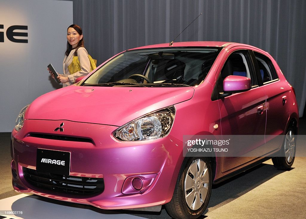 A model poses next to Japan's car manufacturer Mitsubishi Motors new global compact car 'Mirage' in Tokyo on August 1 2012 The Mirage which is...