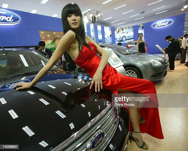 A model poses on a Ford sedan during a family car fair on May 1 2007 in Nanjing of Jiangsu Province China Cars with an engine size of less than 16...