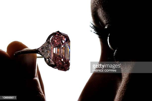 A model poses with a 2478 carat fancy intense pink diamond during a Sotheby's auction preview on November 10 2010 in Geneva The rare pink diamond...