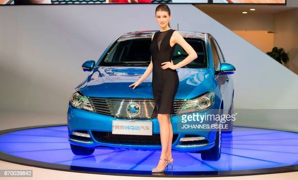 A model poses with a Denza electric car by Chinese automaker Byd a subsidiary firm of German group Daimler during the media day of the 17th Shanghai...