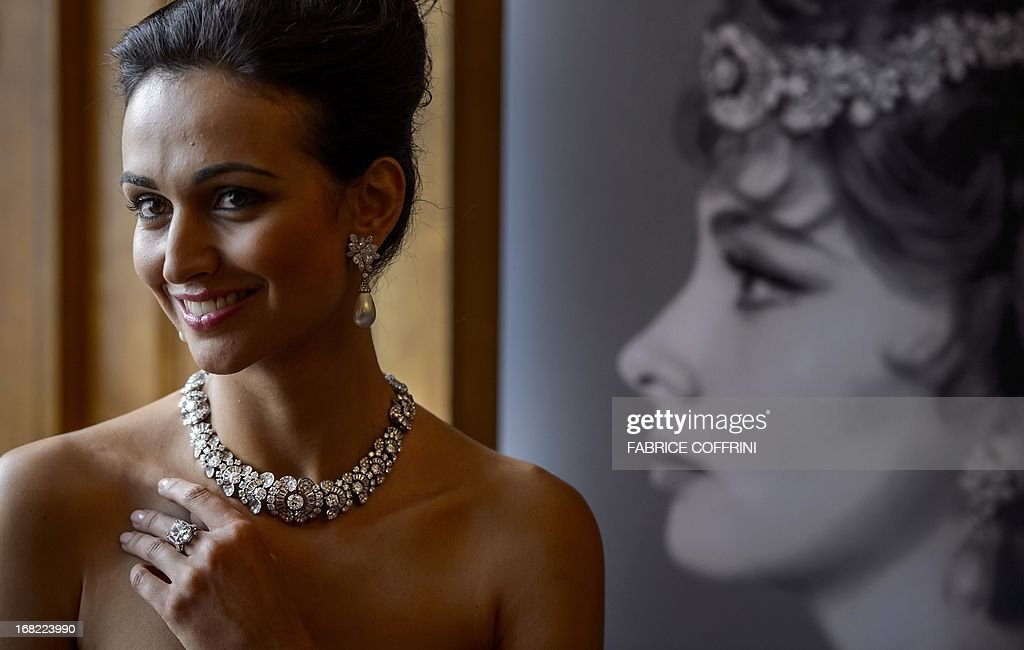 A model poses with a diamond necklace/bracelet combination (estimate CHF 285'000-470'000, USD 300'000-500'000), a pair of natural pearl and diamond pendants (estimate CHF 565'000-940'000, USD 600'000-1'000'000) and a diamond ring set with a cushion-shaped diamond weighing 19.03 carats (estimate CHF 375'000-750'000, USD 400'000-800'000), next to a picture of Italian actress Gina Lollobrigida during a press preview of auction house Sotheby's on May 7, 2013 in Geneva. Lollobrigida is to sell some of her jewellery in Geneva on May 14, 2013 with part of the proceeds going to help stem cell research, auction house Sotheby's said. Designed by Italian creator Bulgari in the 1950s and 1960s, the items include pearl and diamond earrings and a 19.3-carat diamond ring. Both pieces are valued at between $600,000 and one million dollars (465,000 - 775,000 euros). The 85-year-old star of 'The World's Most Beautiful Woman' and 'Come September,' one of Italy's best-known actresses, says she wants to devote herself to sculpture and 'a sculptor doesn't need jewellery', the Sotheby's statement said. AFP PHOTO / FABRICE COFFRINI