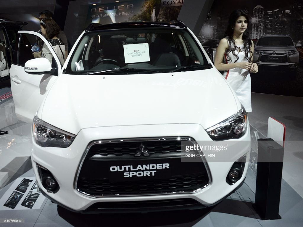 A model poses with a Mitsubishi car on display at the Indonesia International Motor Show in Jakarta on April 8 2016 The annual auto show will take...