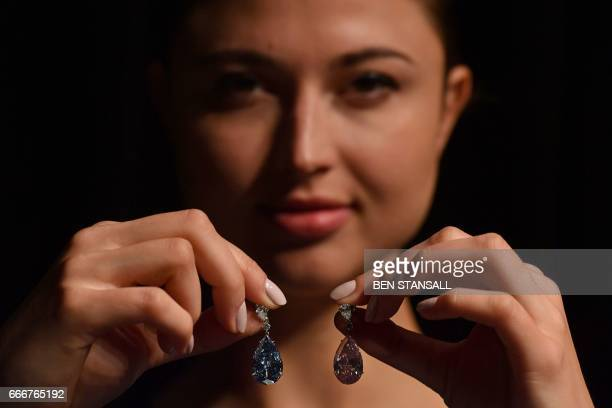 A model poses with a pair of diamond earrings the 1454 carat 'Apollo Blue' and the 16 carat 'Artemis Pink' during a photocall at Sotheby's auction...
