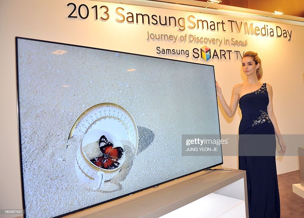 A model poses with a Samsung Electronics' new 75 inch F8000 Smart LED TV during a media conference in Seoul on February 19, 2013. South Korea's Samsung Electronics on February 19 launched a set of giant, Internet-enabled televisions aimed at boosting profit margins and cementing its lead on the world's TV markets hit by slowing global demand. AFP PHOTO / JUNG YEON-JE