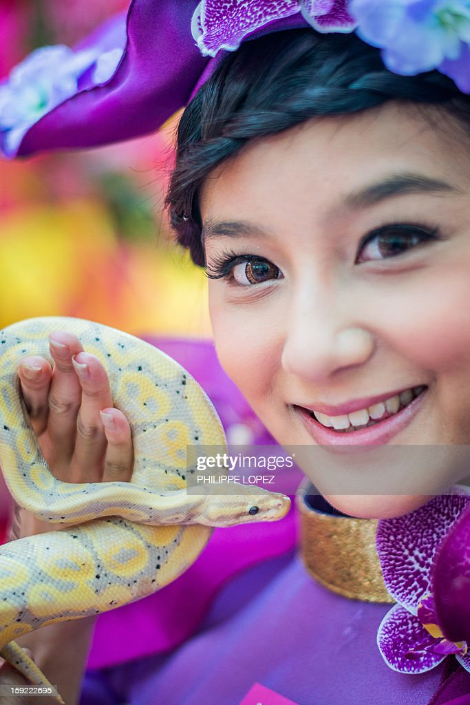 A model poses with a snake during a snake display to promote responsible breeding and pet ownership in Kong Kong on January 10, 2013. The Chinese new year, often referred to as the 'Lunar New Year', will mark the year of the snake on February 10. AFP PHOTO / Philippe Lopez
