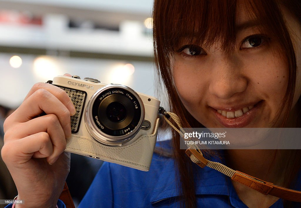 A model poses with an Olympus Pen Lite E-PL5 digital camera during the CP+, (CP plus) photo imaging show in Yokohama on January 31, 2013. Around 96 companies are participating in the exhibition with some 70,000 visitors expected in the four-day-long event.