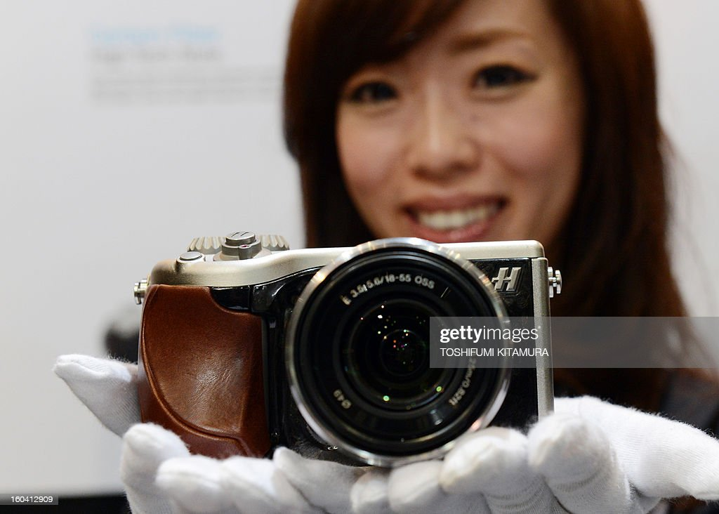 A model poses with Hasselblad's Lunar digital camera digital camera during the CP+, (CP plus) photo imaging show in Yokohama on January 31, 2013. Around 96 companies are participating in the exhibition with some 70,000 visitors expected in the four-day-long event. AFP PHOTO / TOSHIFUMI KITAMURA