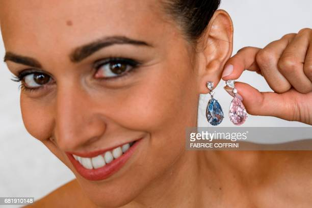 A model poses with the 'The Apollo Blue' and 'The Artemis Pink' diamonds mounted as earrings during a press preview by Sotheby's auction house on May...