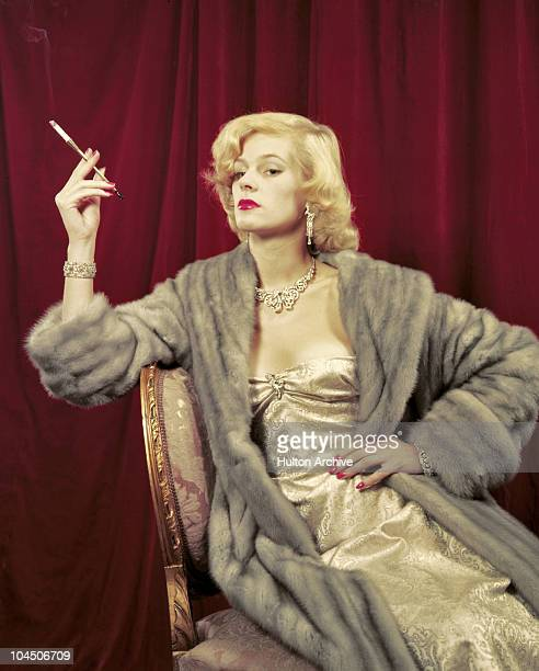 A model posing wearing a silver evening dress a silver/grey mink fur coat and jewellery smoking a cigarette using a cigarette holder circa 1950