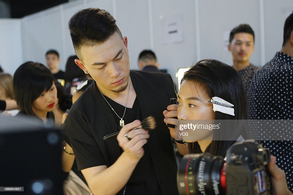 A model prepares backstage ahead of Michael Kors 'Jet Set Experience' event on May 9, 2014 in Shanghai, China.