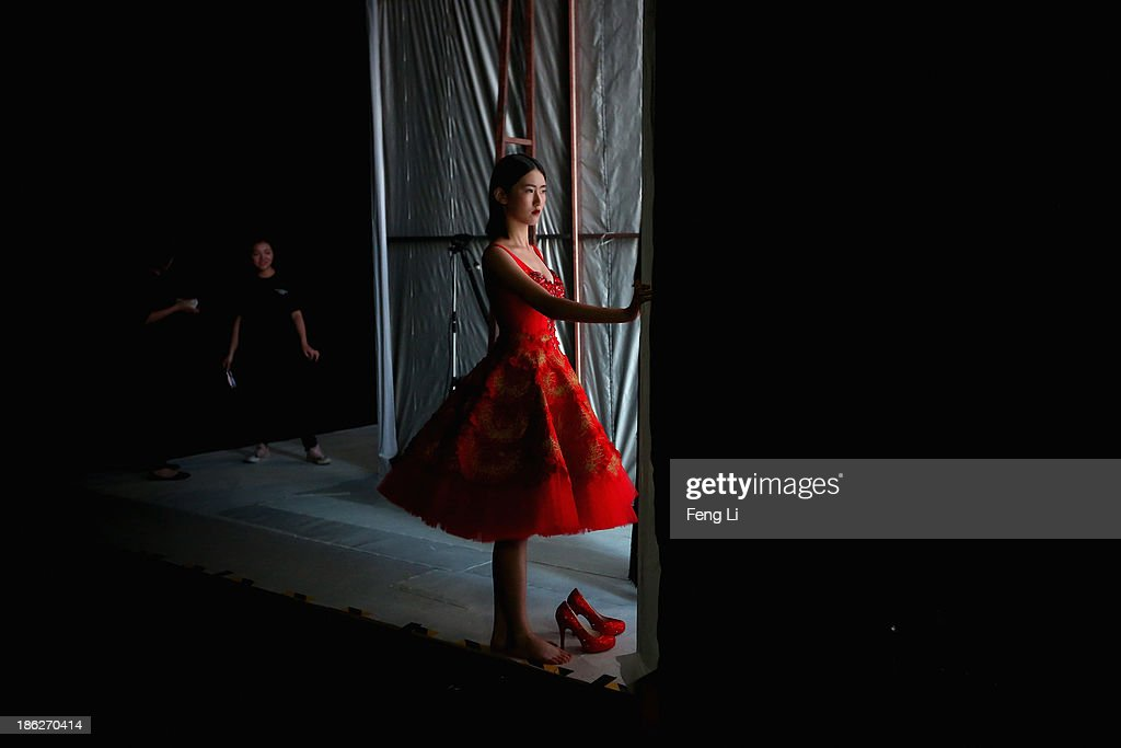 A model prepares backstage ahead of Peng Jing Wedding Dress Collection show during Mercedes-Benz China Fashion Week Spring/Summer 2014 at 751 D-PARK Central Hall on October 27, 2013 in Beijing, China.